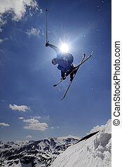 Extreme skier jumping with crossed skis against the blue sky...