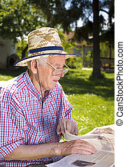 Pensioner with newspaper - Old man reading newspapers in...