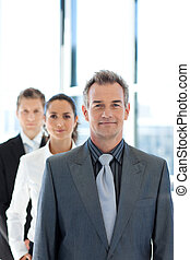 Businessman leading a business team in a line - Mature...