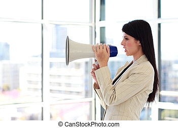 Young businesswoman shouting through megaphone