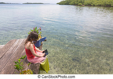 Woman working on the digital tablet at the edge of the pier,...