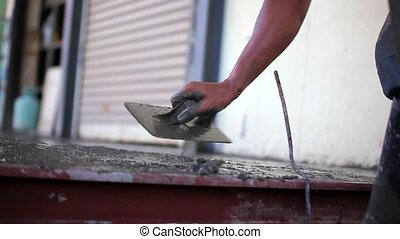 Closeup of masons hand spreading concrete mix with trowel...