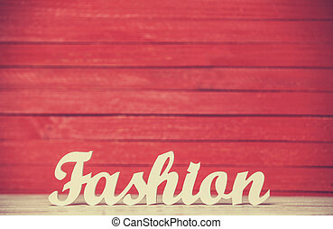 wooden word Fashion on red background.