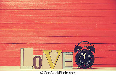 Alarm clock and wooden word Love