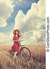 Redhead peasant girl with bicycle on wheat field