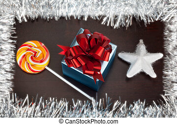 Blue gift box, candycane and white christmas star on black...