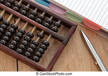 Accounting abacus on wooden table with paper and pen