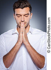 Praying for business. Handsome young man in white shirt holding hands clasped near face while standing against grey background