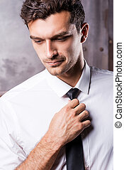 Adjusting his necktie. Handsome young man in formalwear...