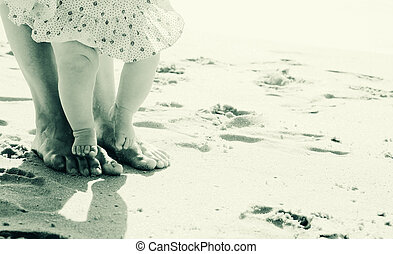mother and baby feet at the beach sand