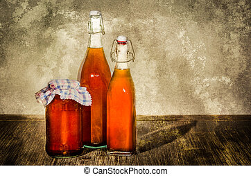 Bottles filled with yellow syrup and jam on kitchen table in...