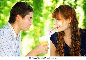 Beautiful Young Couple Drinking Juice from one Glass with...