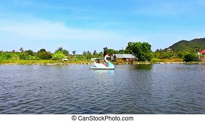 catamaran at form of swan swimming with people  in pond on background Of blue sky and mountains. Video