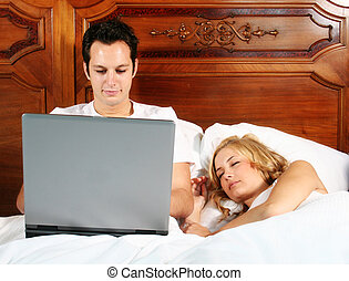 working at bed - a attractive young man is working with his...