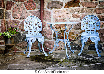 Patio furniture against stone wall - Blue painted metal...