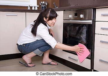 house work - young brunette woman cleaning kitchen