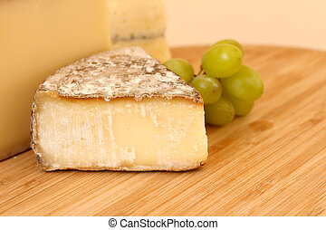Cheese and grapes - Cheese and green grapes on wooden board