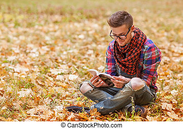 Young relaxed man reading book in nature, back on tree,...
