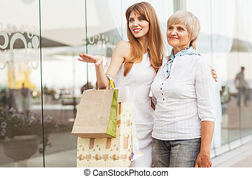 Adult mother and daughter after shopping on the background...