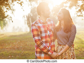 Young couple in love walking in the autumn park near the...