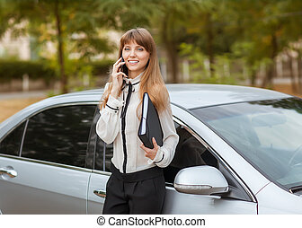Elegant business lady in a grey dress standing in front of her car. She is holding a black folder with documents and talking on the phone.