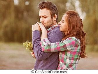 guy kisses the girl's hand in park