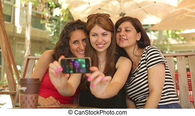 Sidewalk Cafe Selfie - Three girls taking picture of...