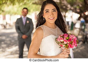 Bride and groom behind her - Portrait of a beautiful Latin...