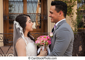 Cute couple outside a church - Profile view of a young bride...