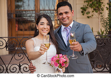 Cheers - Hispanic bride and groom raising their glasses with...