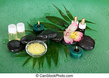 Fragrant oils, salt, candles, stones and flower on big leaf...