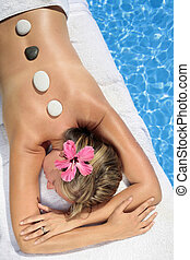 Woman at a Spa - Woman at a spa with white stone on her...