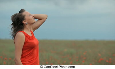 Beautiful Girl in red dress among poppy field looking on the sky