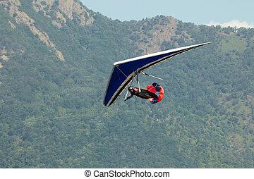 hang glider - man doing hang-gliding and landing with brake...