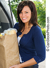 Food - Beautiful Young Woman Loading Groceries Into Her Car