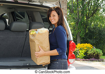 Loading The Car - Young Woman Loading Her Groceries Into The...