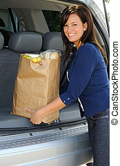 Loading Groceries - Beautiful Young Woman Loading Groceries...