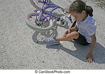 Girl falling off bike - A little girl inspecting her bruise...