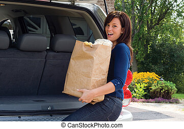 Happy Shopper - Beautiful Young Woman Unloading Shopping...