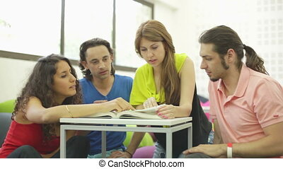 Group Work - Four students looking up information in a huge...