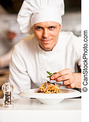 Chef arranging pasta salad in a white bowl - Chef adding...
