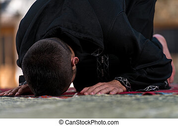 Muslim Man In Dishdasha Is Praying In The Mosque - Young...