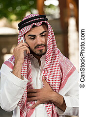 Cheerful Muslim Man Talking On Cell Phone - Young...