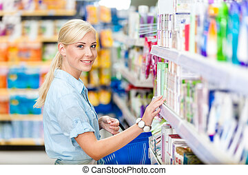 Side view of girl at the shop choosing cosmetics