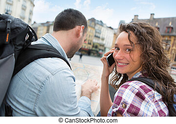 Young couple of tourists booking an activity - View of a...