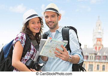 Young couple of tourists visiting city - View of a Young...
