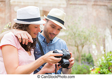 Young couple of tourist watching photographs - View of a...