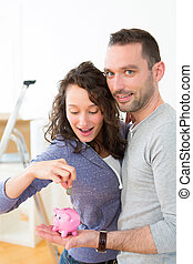 Young couple saving money in a piggy bank - View of a Young...