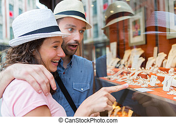 Young couple in love watching jewelry store front - View of...