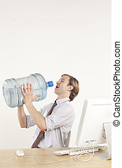 Water break - professional man sitting at desk drinking from...